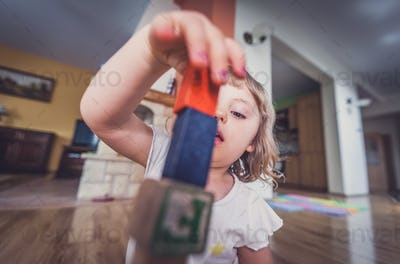 Girl playing with building blocks on floor