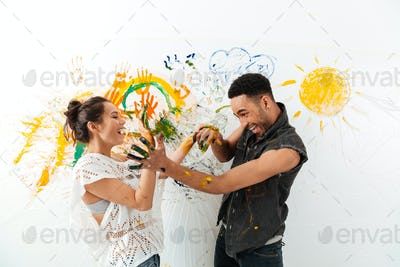 Couple with hands dirty in paints laughing and having fun
