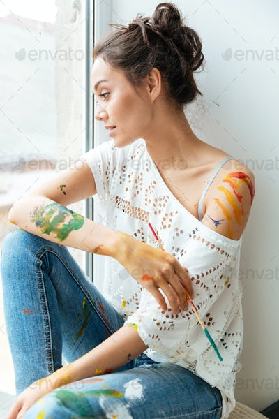 Pensive young woman dirty with paints looking at the window