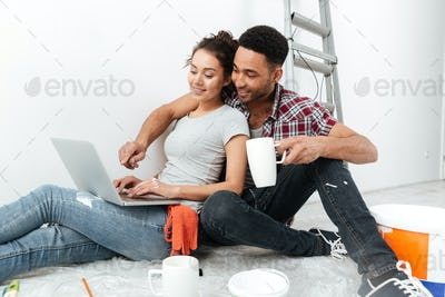 Happy loving couple on floor in new flat using laptop