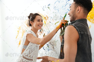 Couple painting with brushes by hands and having fun