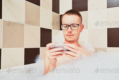 Man using mobile phone in the bathroom
