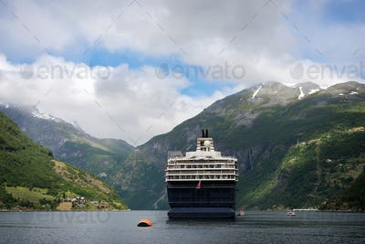 Cruise ship in narrow Geiranger fjord in Norway