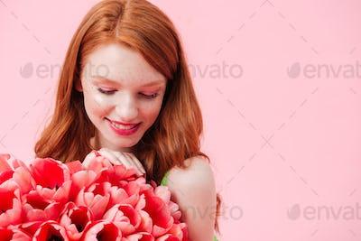 Close up portrait smiling woman holding bouquet of flowers