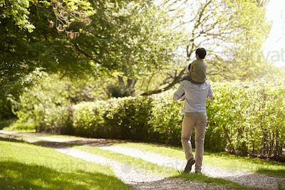 Rear View Of Father Giving Son Ride On Shoulders During Walk