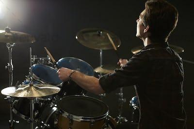 Rear View Of Drummer Playing Drum Kit In Studio