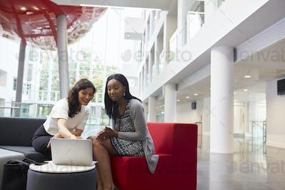 Two Businesswomen Using Laptop In Lobby Of Modern Office