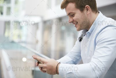 Adult male student using smartphone in university, close up