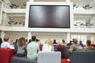 Students watching big screen in university atrium, back view