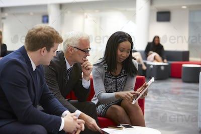 Businesspeople Look At Digital Tablet In Modern Office Lobby