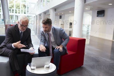 Two Businessmen Discuss Document In Lobby Of Modern Office