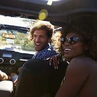 Four friends driving in an open top car, rear passenger POV