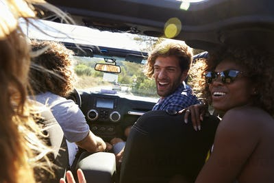 Four friends driving in an open top car, rear passenger POV