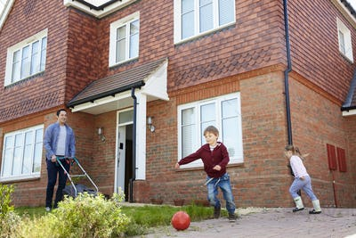 Children Play In Garden As Father Mows Lawn Outside House