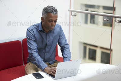 Middle aged black man uses laptop on mezzanine, elevated view