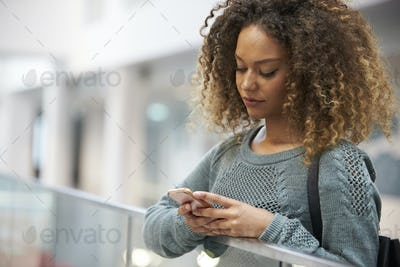 Smiling mixed race young woman uses phone in modern interior