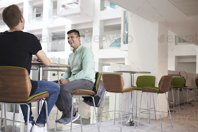 Adult male students talking at a university cafe, low angle