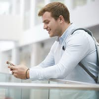 Adult male student using smartphone in university interior