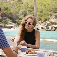 Young couple sitting with lunch at a table by the sea, Ibiza