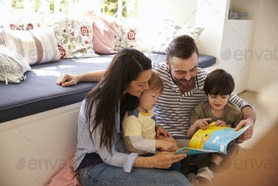Family Sitting On Floor Reading Story At Home Together