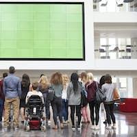 Students looking up at a big screen in university atrium