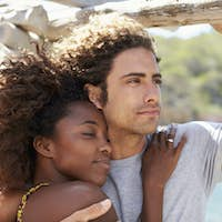 Mixed race couple talking at table by the sea, Ibiza, Spain
