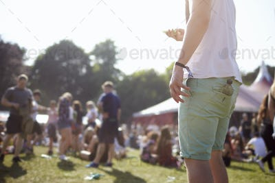 Close Up Of Man Using Mobile Phone At Music Festival