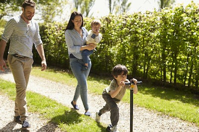 Family Going For Walk In Summer Countryside