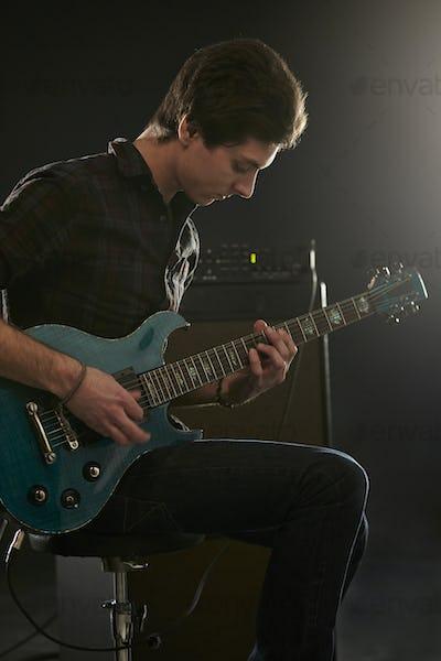 Man Playing Electric Guitar In Studio