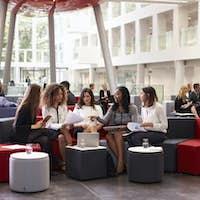 Businesswomen Meeting In Busy Lobby Of Modern Office