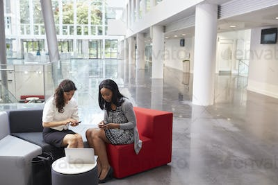 Two Businesswomen Using Mobile Phones In Lobby Of Office