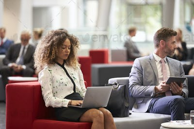Businesspeople Using Digital Devices In Busy Office Lobby