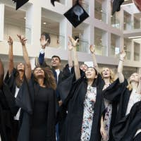 University students throwing their caps in the air on graduation day