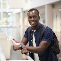 Smiling black male student in modern university, portrait