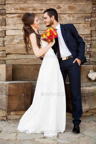 Happy groom embracing his wife in their wedding day