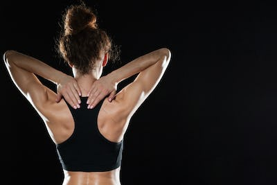 Back view of Strong fitness woman posing in studio