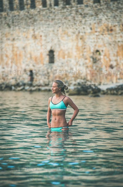 Young woman tourist swimming at beach near ancient fortress wall