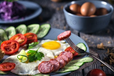 Fried eggs with vegetables and sausage on table