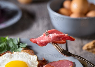 Piece of delicious bacon on fork over plate with eggs