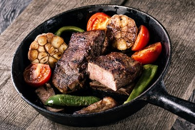 Juicy steak with vegetable garnish on an old frying pan