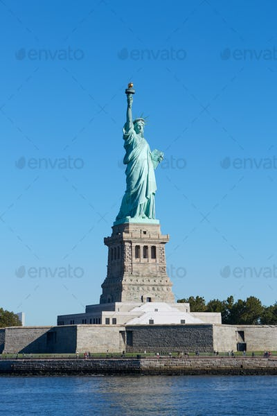 Statue of Liberty and Liberty Island in a sunny day, blue sky