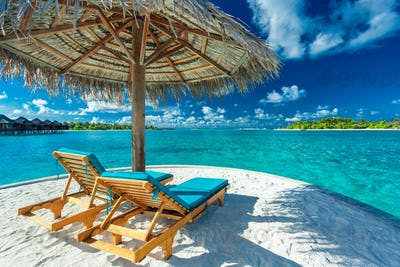 Two beach chairs under umbrella with ocean view in Maldives