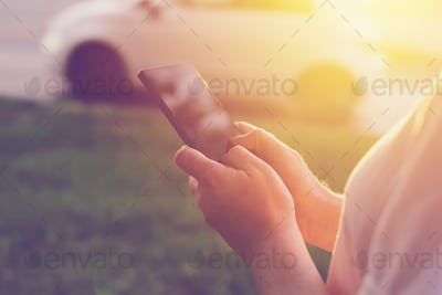 Woman using mobile phone app to call taxi cab