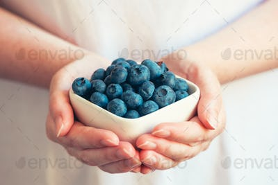 Woman offering blueberries