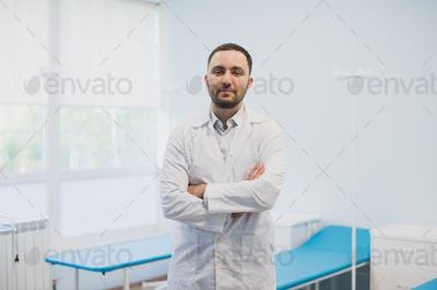 Portrait of a happy male doctor standing with arms crossed at medical office