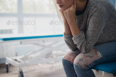 Woman's hand waiting for doctor in hospital feeling worried.