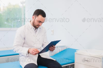 Portrait of handsome young doctor in office