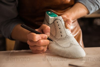 Close up of a male shoemaker drawing design