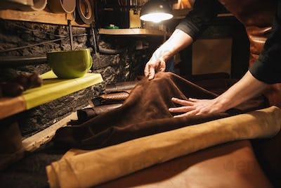 Young man shoemaker at footwear workshop.