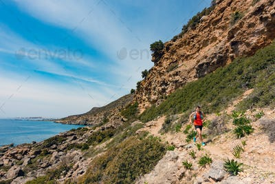 Man running in inspirational mountains and seaside